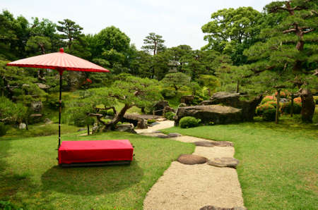 Red umbrella and bench in a Japanese garden
