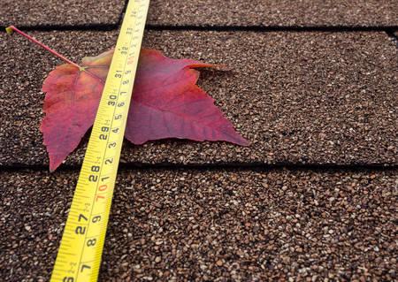 asphalt shingles: Tape measure and autumn leaf on asphalt shingles