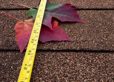 asphalt shingles: Tape measure and autumn leaves on asphalt shingles