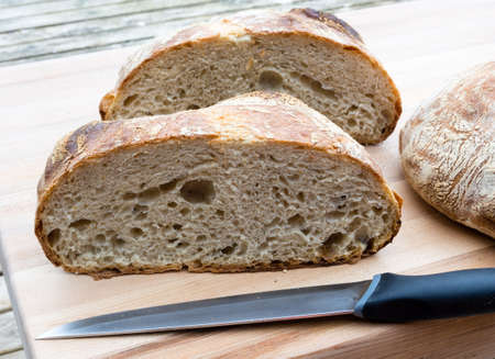 french boule: Round french boule bread cut in half with knife Stock Photo