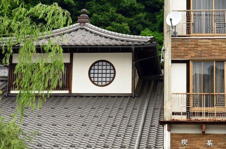 round window: Kinosaki, Japan - June 15, 2010: Traditional Japanese house with round window side by side with modern house Editorial