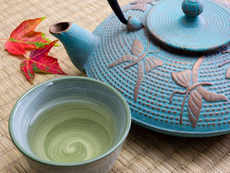 tea ceremony: Oriental cast iron tea pot with tea cup and autumn leaves on tatami mat Stock Photo