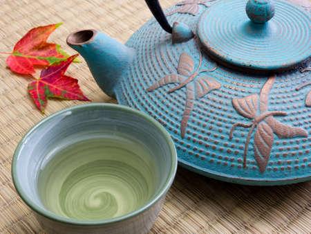 taza de te: Oriental cast iron tea pot with tea cup and autumn leaves on tatami mat Foto de archivo