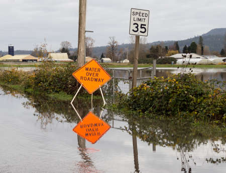 flooded: Flooded road with water over roadway sign