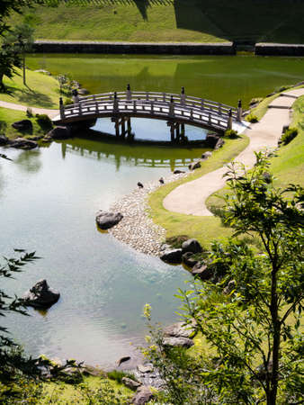 arched: Traditional Japanese garden with pond and wooden arched bridge