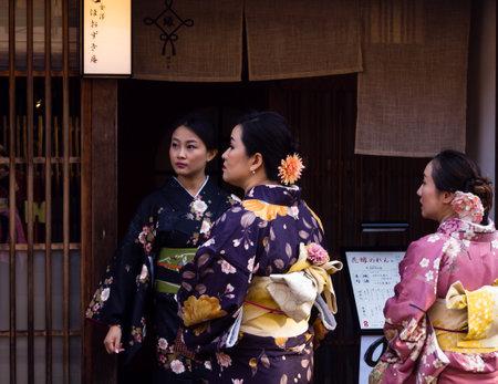 geisha kimono: Kanazawa, Japan - September 29, 2015: Group of asian women in colorful kimono in front of traditional Japanese house in historic Higashi Chaya geisha district