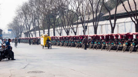velo: Beijing, China - March 26, 2015: Pedicabs lined up on a street in historic downtown Beijing