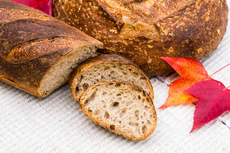 french boule: Slices of homemade artisan bread with red fall leaves