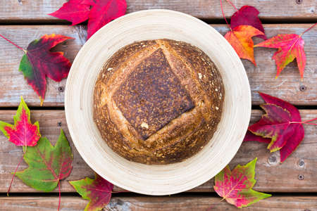 french boule: Homemade artisan bread on a round plate with fall decorations Stock Photo