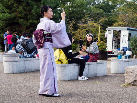 croud: Kyoto, Japan - September 30, 2015: Young girl in colorful kimono taking pictures with smartphone in Maruyama park Editorial