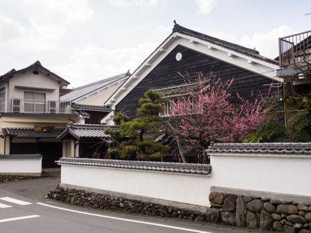 Uchiko, Japan - March 03, 2013: Traditional Edo period merchant house in historic Uchiko town, with plum tree blooming in the garden Redakční