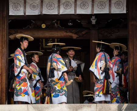 Takayama, Japan - October 9, 2015: Local dancers in traditional costumes at the entrance to Hachimangu shrine during annual Takayama festival, one of the most famous festivals in Japan Editorial