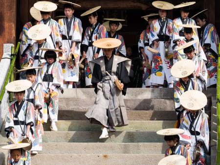 Takayama, Japan - October 9, 2015: Group of local performers in traditional costumes coming out of Hachimangu shrine during annual Takayama festival, one of the most famous festivals in Japan Editorial