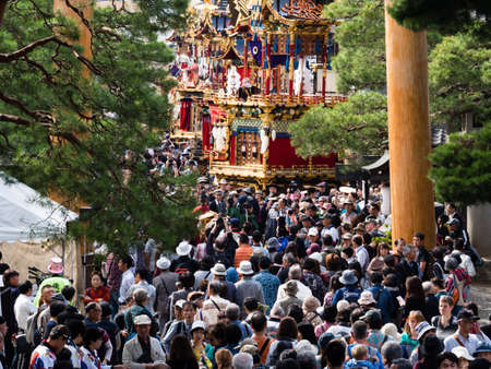 Takayama, Japan - October 9, 2015: Crowd of visitors at the entrance to Hachimangu shrine during annual Takayama Autumn Festival, one of the most famous festivals in Japan