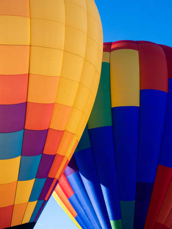 Two colorful hot air balloons on the ground ready to take off - at Winthrop Balloon Festival, Washington state