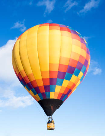 Colorful hot air balloon flying in the bright blue sky during Winthrop Balloon Festival in Washington state Фото со стока