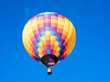 Colorful hot air balloon flying in the bright blue sky during Winthrop Balloon Festival in Washington state 스톡 콘텐츠