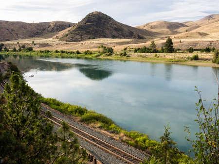 Railroad tracks running along scenic and wild Flathead river near Perma, Montana, USA
