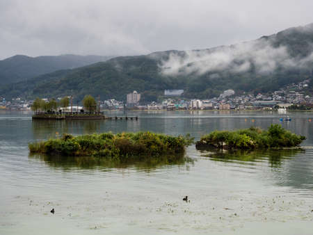 Rainy day on Lake Suwako with heavy clouds covering the surrounding mountains - Kamisuwa, Nagano prefecture, Japan