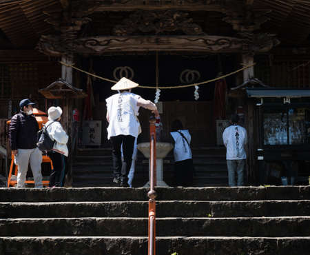 Kochi, Japan - April 7, 2018: O-henro pilgrim climbing the stairs leading to the main hall of Kiyotakiji, temple number 35 of Shikoku pilgrimage