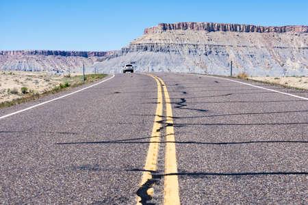 Car driving on scenic state route 24 running through desert near Caineville - Utah, USA