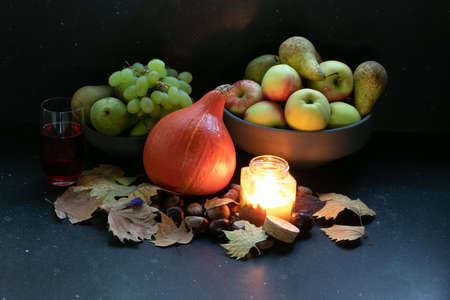 Organic orange pumpkin in a composition with grapes, peers, apples, autumn dried leaves, wine, candle light in a dark marble background. Harvest and cold times