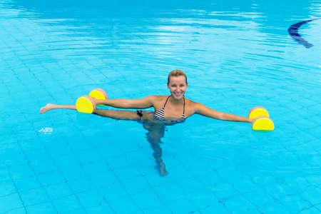 aerobics class: Woman is engaged aqua aerobics in water