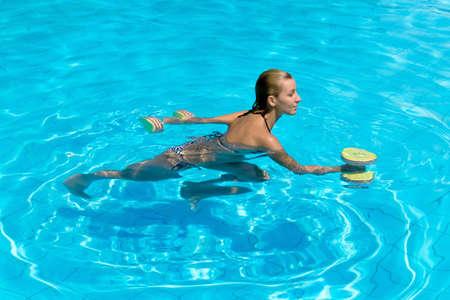 aerobics: Aqua aer�bicos, mujer en el agua con pesas