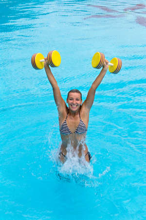 Aqua aerobic. Woman is engaged aqua aerobics in water 스톡 콘텐츠