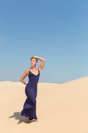 sensuality: beautiful adult sensuality woman in dress on blue sky and sand background Stock Photo
