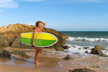 Beautiful sexy young woman surfer girl in bikini with white surfboard on a beach photo