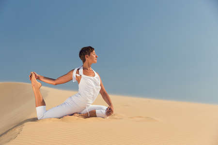 Yoga meditation on the beach, healthy female body in peace, woman sitting relaxed on sand over beautiful sea sunset, calm girl enjoying nature, active vacation lifestyle, zen spa, wellness concept photo