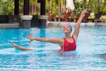 Aqua-Aerobic. Synchronisierte Schwimmerin Stretching am Pool Standard-Bild