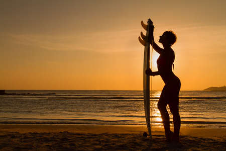 bodyboarding: Rear view of beautiful sexy young woman surfer girl in bikini with white surfboard on a beach at sunset or sunrise