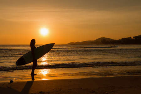 surf: Rear view of beautiful sexy young woman surfer girl in bikini with white surfboard on a beach at sunset or sunrise