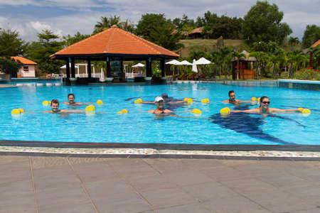 Aqua aerobic. Smiling group doing aqua aerobics in swimming pool with dumbbells