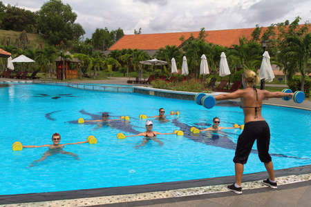 aerobics class: Aqua aerobic. Aqua Gym: aerobics  fitness instructor in front of a group of people in the water performing exercises.