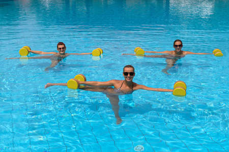 outdoor training: Aqua aerobic. Happy active fitness people doing exercise with aqua dumbbell in a swimming pool Stock Photo