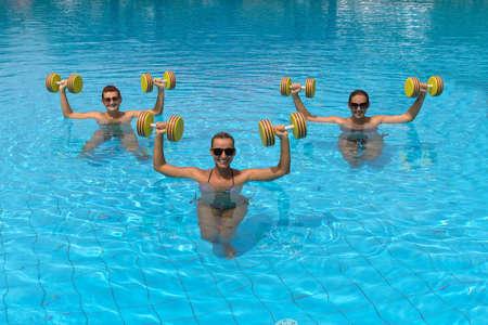 aerobics: Aer�bico Aqua. Gente de la aptitud activos felices que hacen ejercicio con mancuerna aqua en una piscina Foto de archivo