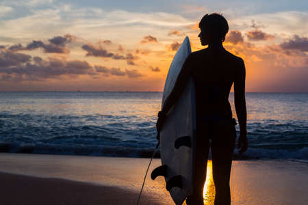 woman surfer with surfboard on tropical beach at sunset photo