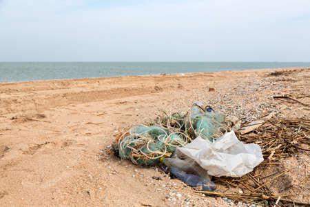 wastes: Pollution: garbages, plastic, and wastes on the beach after winter storms. Azov sea. dolganka