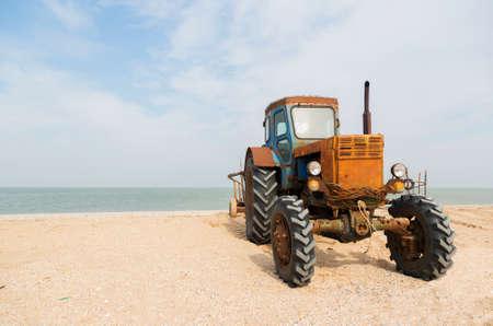 azov sea: old orange tractor on the sandy beach. Azov sea. dolganka