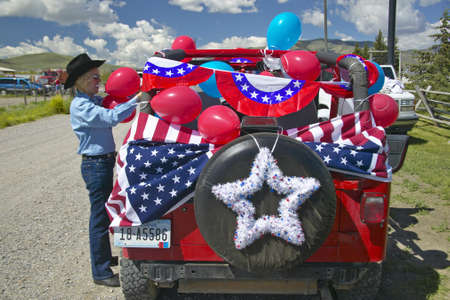 Woman decorating her car in red, white & blue in Lima Montana Stock Photo - 19962344