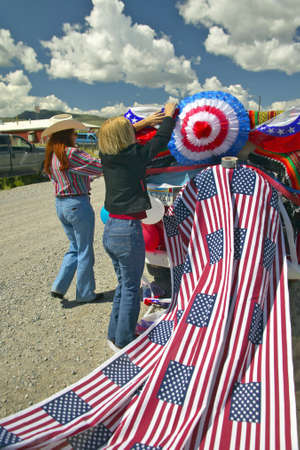 Women decorating a car in red, white & blue in Lima Montana