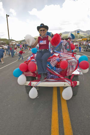 middle america: Woman sitting on the hood of a jeep decorated for the Fourth of July, in Lima Montana