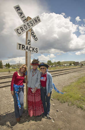 Three women at a railroad crossing dressed for the Fourth of July,in Lima Montana Stock Photo - 19962226