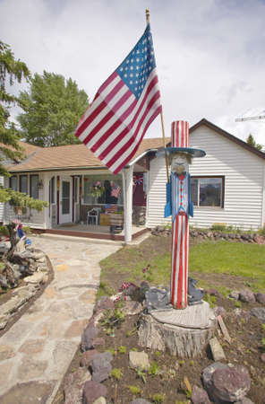 middle america: Country home with an Uncle Sam wood carving and American flag Editorial