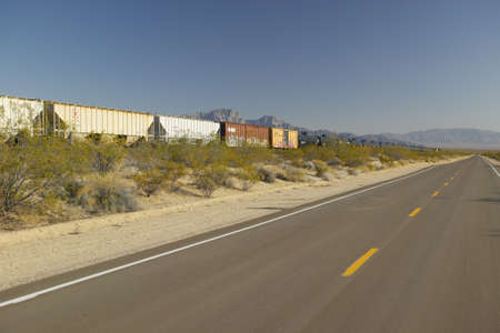 Freight train travels through desert and mountainous areas of Mojave Desert in Southern California
