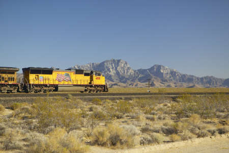 Freight train travels through desert and mountainous areas of Mojave Desert in Southern California photo