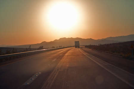 18-wheeler semi-trucks at sunset hit the highway driving down Interstate Highway 15 between Los Angeles and Las Vegas Nevada.